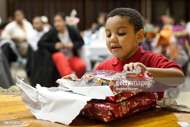 Donovan Gonzalez age six opens a gift during a Christmas dinner hosted by Engine 277 Ladder 112 of the Fire Department of New York on December 25...