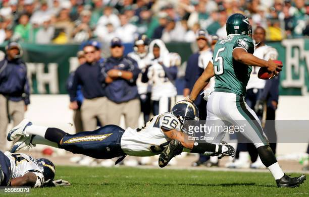 Donovan McNabb of the Philadelphia Eagles scrambles to avoid a diving Shawne Merriman of the San Diego Chargers on October 23 2005 at Lincoln...