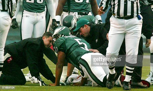 Donovan McNabb starting quarterback for the Philadelphia Eagles is checked by Eagles trainers and teammates after being sacked by two Arizona...