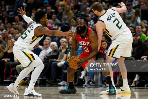 Donovan Mitchell and Joe Ingles of the Utah Jazz guard James Harden of the Houston Rockets during a game at Vivint Smart Home Arena on February 22,...