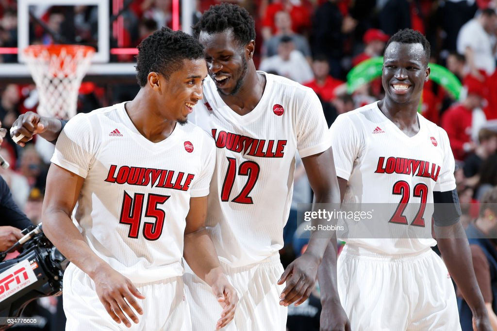 Donovan Mitchell #45, Mangok Mathiang #12 and Deng Adel #22 of the Louisville Cardinals celebrate after the game against the Miami Hurricanes at KFC YUM! Center on February 11, 2017 in Louisville, Kentucky. Louisville defeated Miami 71-66.