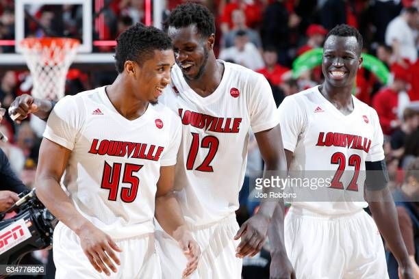 Donovan Mitchell Mangok Mathiang and Deng Adel of the Louisville Cardinals celebrate after the game against the Miami Hurricanes at KFC YUM Center on...