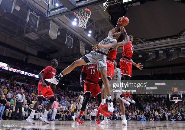 Donovan Mitchell of the Louisville Cardinals blocks a shot by John Collins of the Wake Forest Demon Deacons during the game at the LJVM Coliseum...