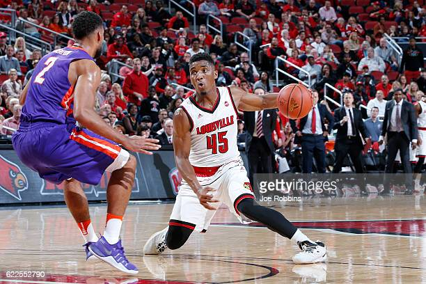 Donovan Mitchell of the Louisville Cardinals handles the ball against Christian Benzon of the Evansville Purple Aces in the first half of the game at...