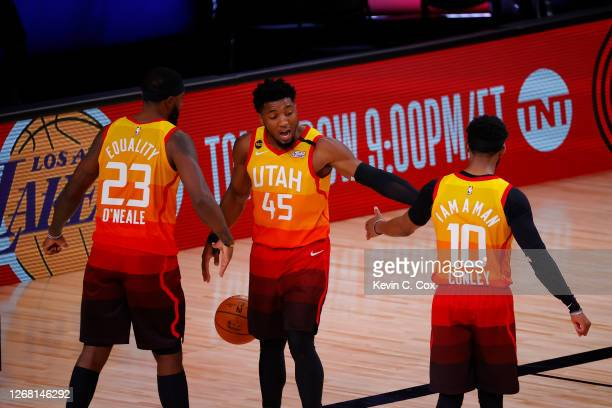 Donovan Mitchell of the Utah Jazz celebrates a win against the Denver Nuggets with teammates Royce O'Neale and Mike Conley following Game Four of the...