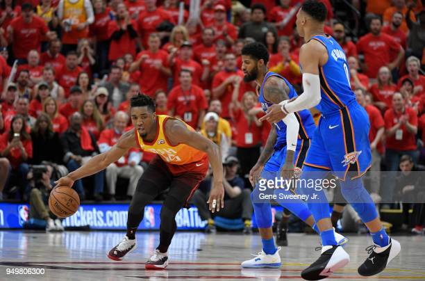 Donovan Mitchell of the Utah Jazz dribbles around Paul George and Russell Westbrook of the Oklahoma City Thunder in the second half during Game Three...