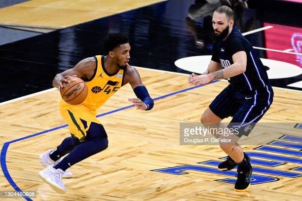 Donovan Mitchell of the Utah Jazz dribbles the ball as Evan Fournier of the Orlando Magic defends during the third quarter at Amway Center on...