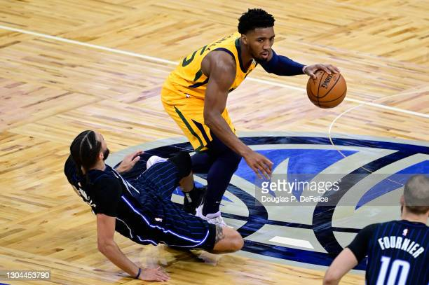 Donovan Mitchell of the Utah Jazz dribbles the ball as he is fouled by Michael Carter-Williams of the Orlando Magic during the second quarter at...