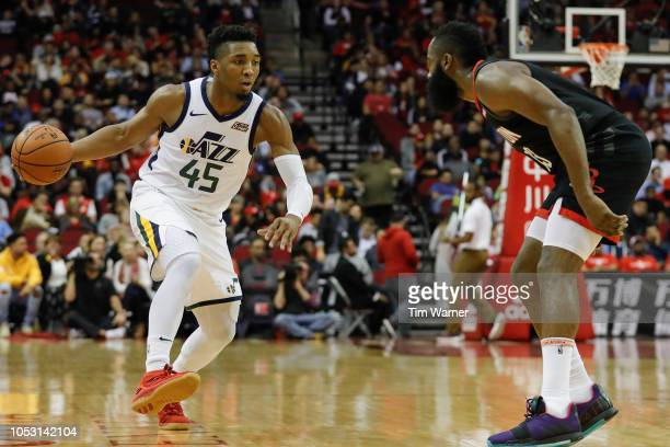 Donovan Mitchell of the Utah Jazz dribbles the ball defended by James Harden of the Houston Rockets in the first half at Toyota Center on October 24...