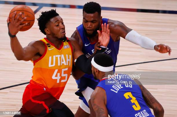 Donovan Mitchell of the Utah Jazz drives against Paul Millsap and Torrey Craig of the Denver Nuggets during the fourth quarter in Game Four of the...