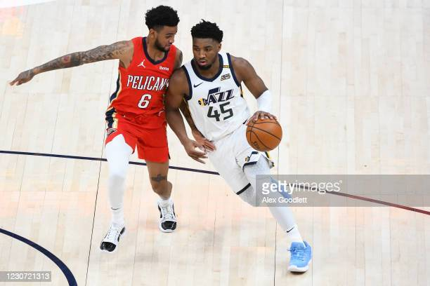 Donovan Mitchell of the Utah Jazz drives into Nickeil Alexander-Walker of the New Orleans Pelicans during a game at Vivint Smart Home Arena on...
