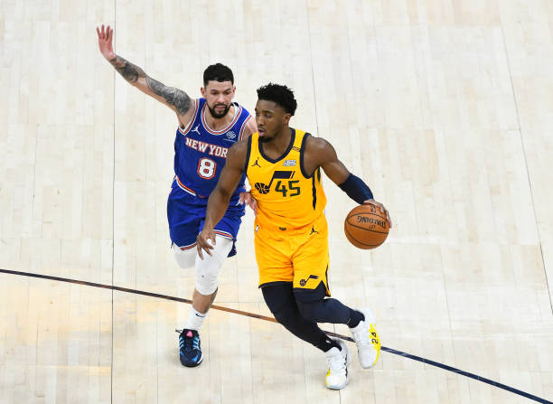 Donovan Mitchell of the Utah Jazz drives past Austin Rivers of the New York Knicks during a game at Vivint Smart Home Arena on January 26, 2021 in...