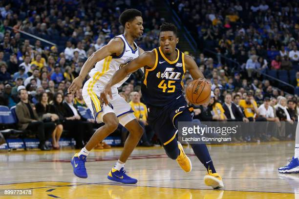 Donovan Mitchell of the Utah Jazz drives to the basket past Patrick McCaw of the Golden State Warriors at ORACLE Arena on December 27 2017 in Oakland...