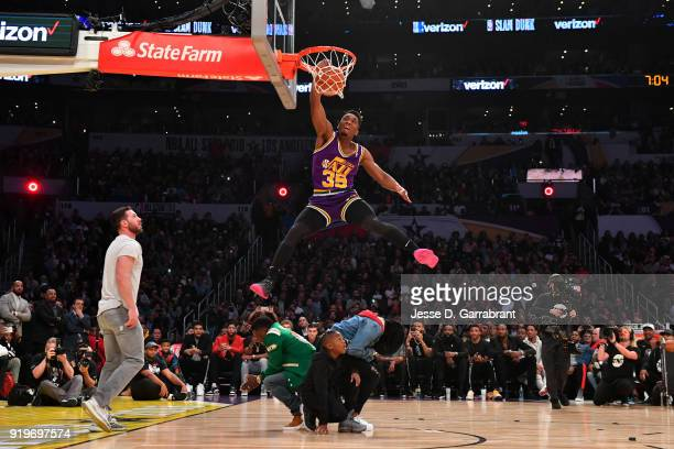 Donovan Mitchell of the Utah Jazz dunks over Kevin Hart and crew during the Verizon Slam Dunk Contest during State Farm AllStar Saturday Night as...