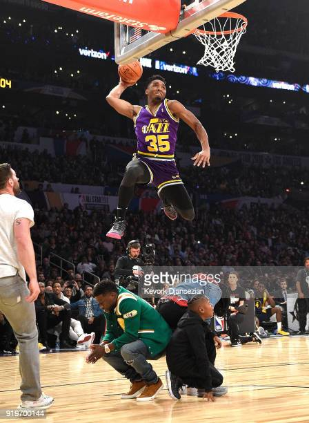 Donovan Mitchell of the Utah Jazz dunks over Kevin Hart Jordan Mitchell and Hendrix Hart in the 2018 Verizon Slam Dunk Contest at Staples Center on...