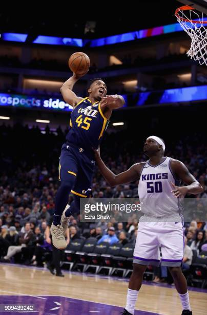 Donovan Mitchell of the Utah Jazz dunks over Zach Randolph of the Sacramento Kings at Golden 1 Center on January 17 2018 in Sacramento California...