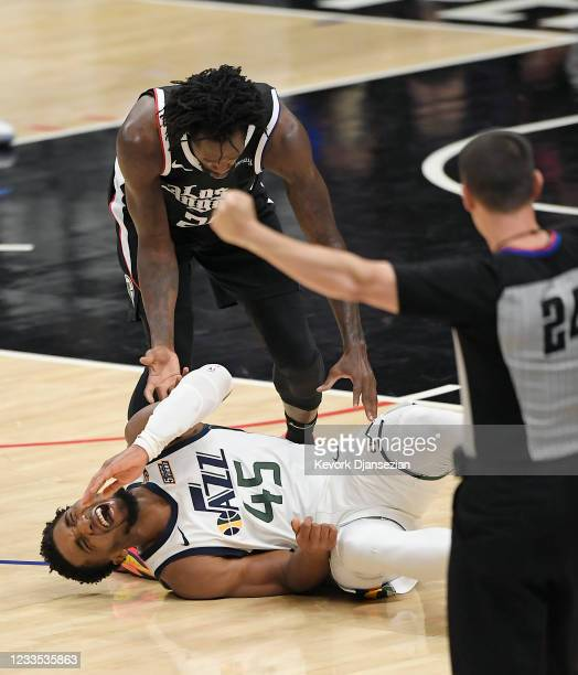 Donovan Mitchell of the Utah Jazz grimaces in pain after falling with Patrick Beverley of the Los Angeles Clippers looking on during the second half...