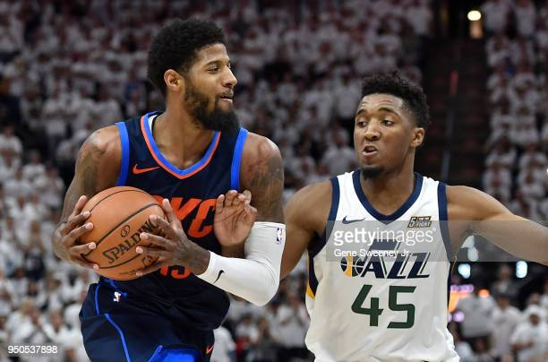Donovan Mitchell of the Utah Jazz guards Paul George of the Oklahoma City Thunder during Game Four of Round One of the 2018 NBA Playoffs at Vivint...