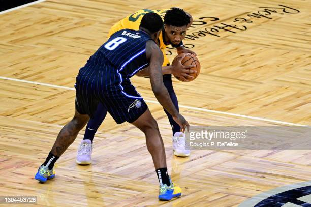 Donovan Mitchell of the Utah Jazz handles the ball as Dwayne Bacon of the Orlando Magic defends during the second quarter at Amway Center on February...