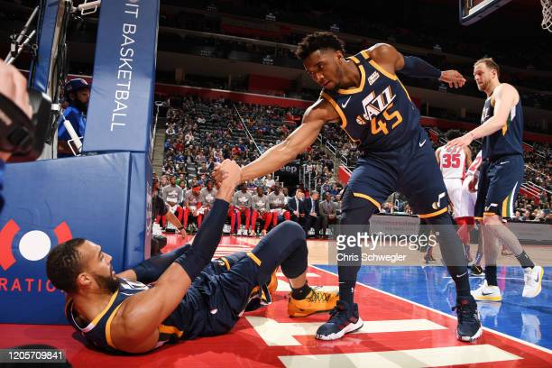 Donovan Mitchell of the Utah Jazz helps Rudy Gobert of the Utah Jazz from the floor on March 7 2020 at Little Caesars Arena in Detroit Michigan NOTE...