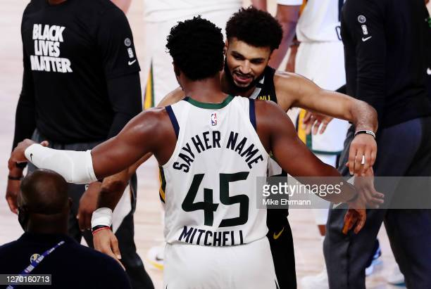 Donovan Mitchell of the Utah Jazz hugs Jamal Murray of the Denver Nuggets after the game ends and the Denver Nuggets wiin Game Seven of the Western...