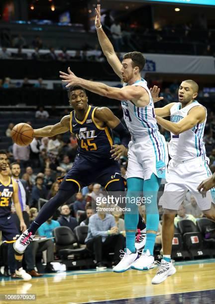 Donovan Mitchell of the Utah Jazz looks to pass around teammates Frank Kaminsky and Nicolas Batum of the Charlotte Hornets during their game at...