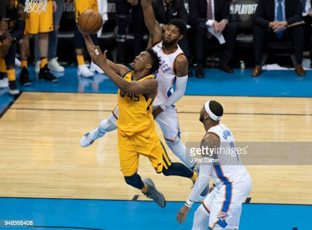 Donovan Mitchell of the Utah Jazz scores two points as Paul George of the Oklahoma City Thunder and Carmelo Anthony of the Oklahoma City Thunder...