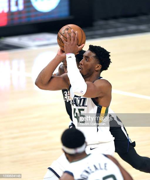 Donovan Mitchell of the Utah Jazz shoots and scores a three-point basket against Patrick Beverley of the Los Angeles Clippers during the first half...