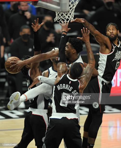 Donovan Mitchell of the Utah Jazz throws an outlet pass under pressure from Paul George and Marcus Morris Sr. #8 of the Los Angeles Clippers during...