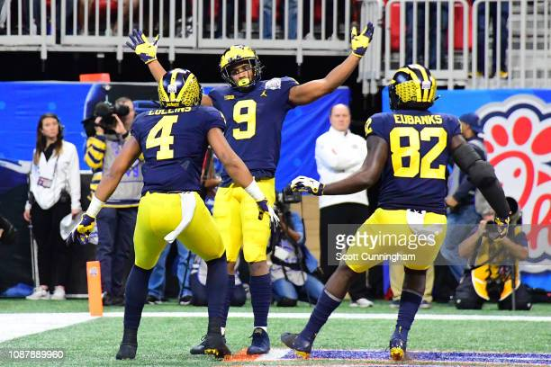 Donovan PeoplesJones of the Michigan Wolverines is congratulated by his teammates Nico Collins and Nick Eubanks after scoring a first quarter...