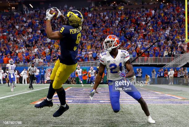 Donovan PeoplesJones of the Michigan Wolverines scores a first quarter touchdown reception against Trey Dean III of the Florida Gators during the...