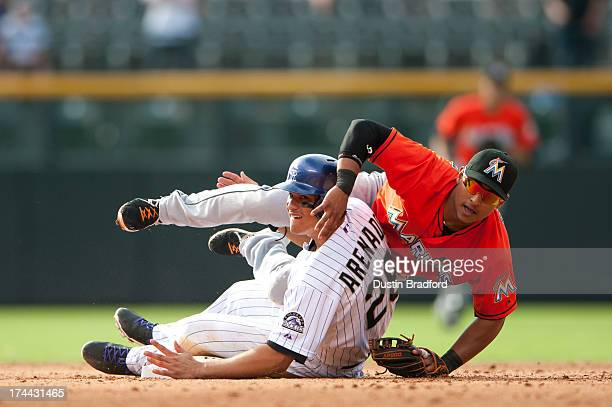 Donovan Solano of the Miami Marlins and Nolan Arenado of the Colorado Rockies looks towards first base after they became tangled as Solano turned a...