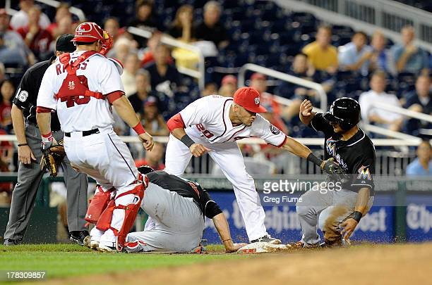 Donovan Solano of the Miami Marlins is safe at third base after Logan Morrison was tagged out in the sixth inning by Ian Desmond of the Washington...