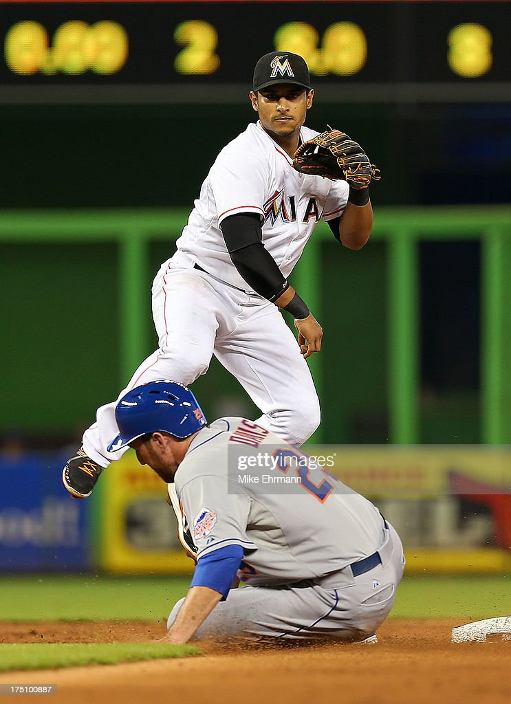Donovan Solano #17 of the Miami Marlins turns a double play as Ike Davis #29 of the New York Mets slides into second during a game at Marlins Park on July 31, 2013 in Miami, Florida.