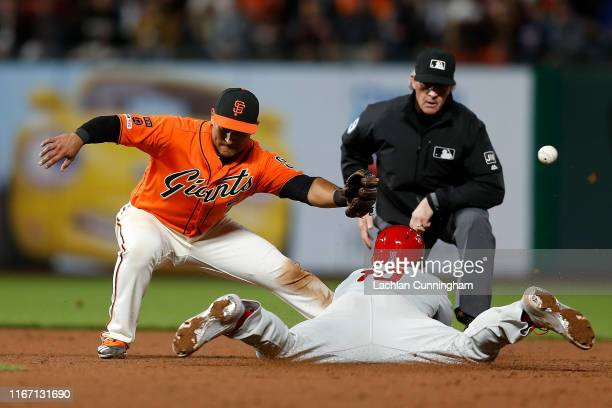Donovan Solano of the San Francisco Giants is unable to field a throw as J.T. Realmuto of the Philadelphia Phillies steals second base in the top of...