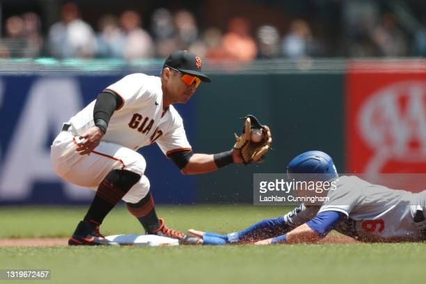 Donovan Solano of the San Francisco Giants tags out Gavin Lux of the Los Angeles Dodgers in the top of the first inning at Oracle Park on May 23,...