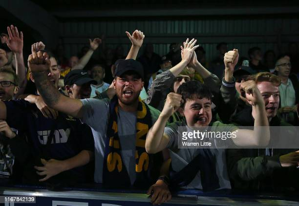 Dons fans celebrate their teams victory after a penalty shoot out during the Carabao Cup First Round match between AFC Wimbledon and Milton Keynes at...