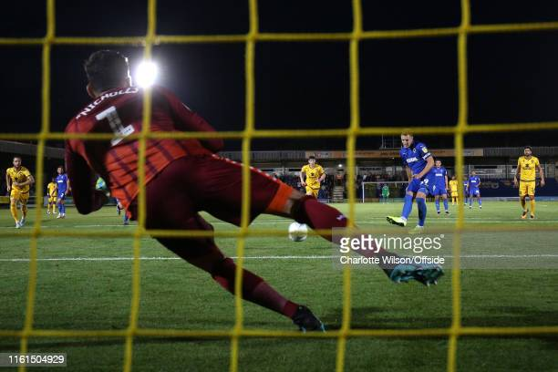 Dons goalkeeper Lee Nicholls saves the penalty of Joe Pigott of Wimbledon during the Carabao Cup First Round match between AFC Wimbledon and Milton...
