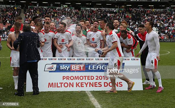Dons players celebrate after gaining promotion to the Championship at the end of the Sky Bet League One match between MK Dons and Yeovil Town at...