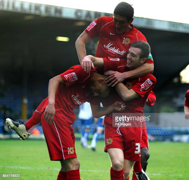 MK Dons's Mark Wright celebrates his first goal with teammates Keith Andrews Jordan Hadfield during the League Two match at Gigg Lane Bury