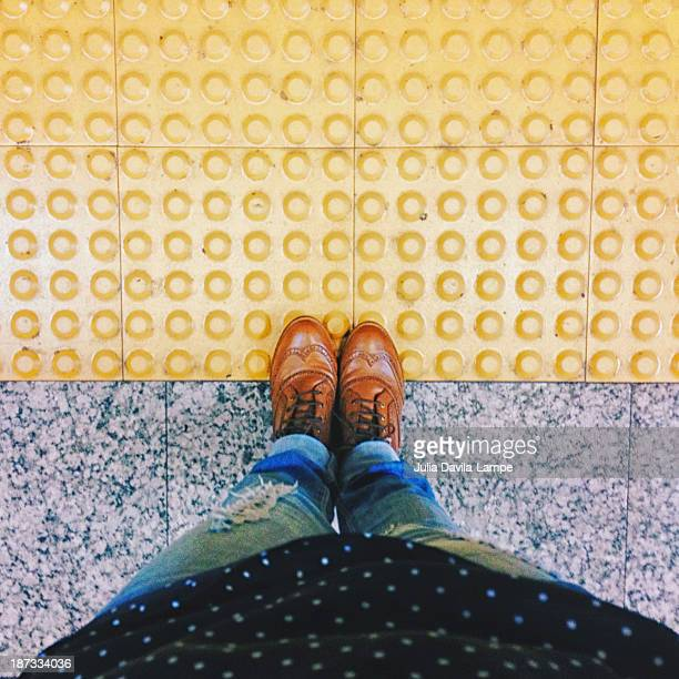 don't cross the line before train stops - lunares fotografías e imágenes de stock