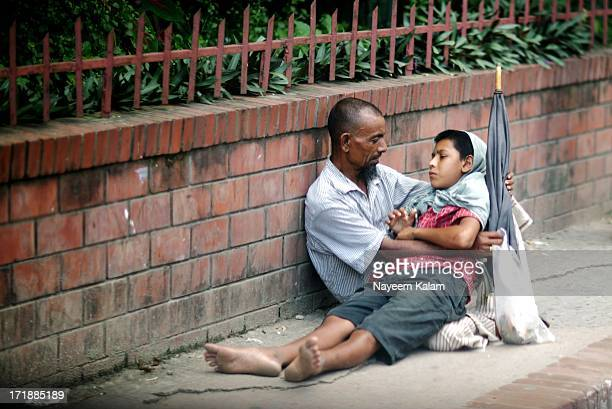 Dont know what happened but I am sure the son is sick and the father is looking for help sitting in that pavement.... I think they are two beautiful...