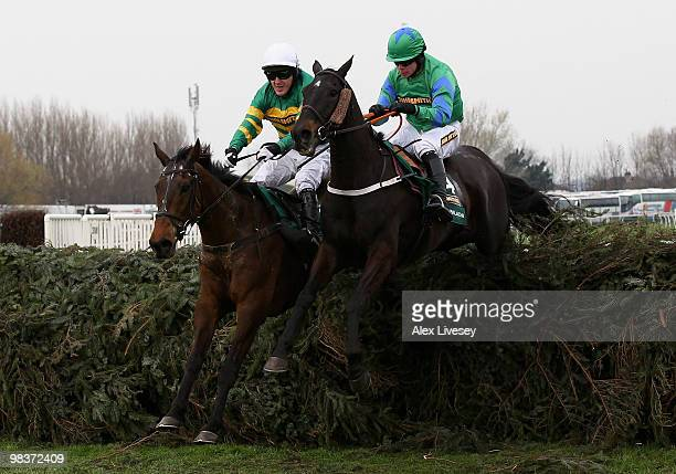 Don't Push It ridden by AP McCoy clears the last fence alongside Black Apalachi ridden by Denis O'Regan on their way to victory in The John Smith's...