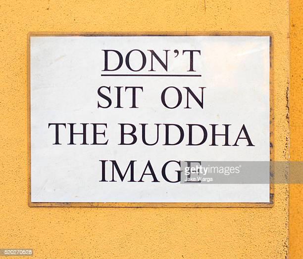 don't sit on buddha sign, bangkok, thailand - jake warga stock pictures, royalty-free photos & images