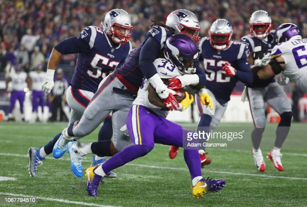 Dont'a Hightower of the New England Patriots tackles Dalvin Cook of the Minnesota Vikings during the first half at Gillette Stadium on December 2...
