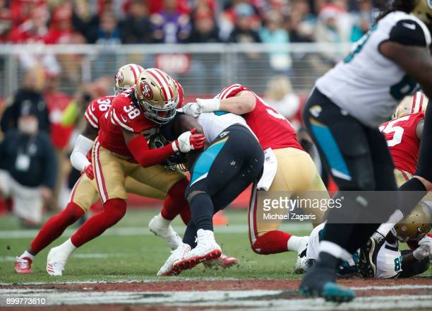 Dontae Johnson and Brock Coyle of the San Francisco 49ers tackle Leonard Fournette of the Jacksonville Jaguars during the game at Levi's Stadium on...