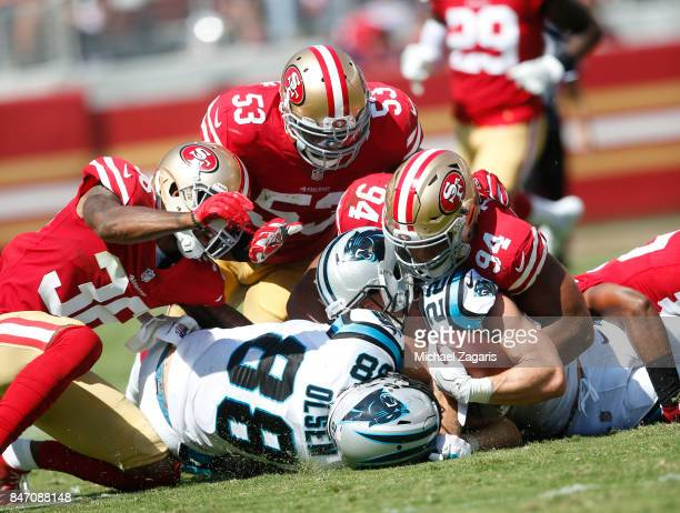 Dontae Johnson NaVorro Bowman and Solomon Thomas of the San Francisco 49ers tackle Christian McCaffrey of the Carolina Panthers during the game at...