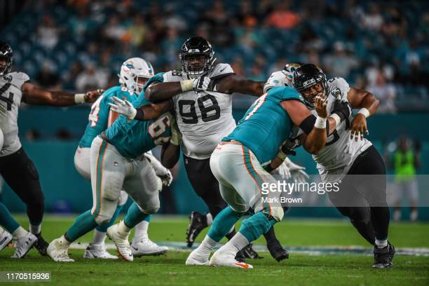 Dontavius Russell and Mike Hughes of the Jacksonville Jaguars in action during the preseason game against the Miami Dolphins at Hard Rock Stadium on...