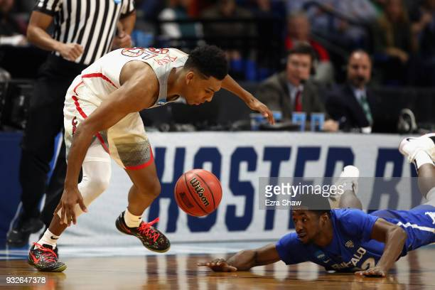 Dontay Caruthers of the Buffalo Bulls and Allonzo Trier of the Arizona Wildcats battle for the ball in the second half during the first round of the...