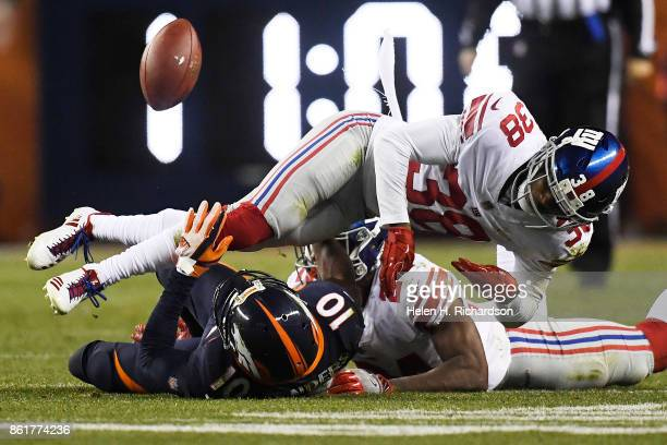 Donte Deayon of the New York Giants and Eli Apple break up a pass intended for Emmanuel Sanders of the Denver Broncos during the third quarter of the...